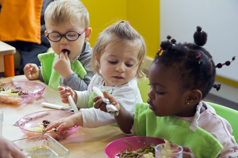 3 jeunes enfants mangent avec les doigts à table.